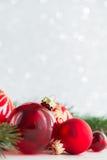 Röda prydnader och xmas-trädet blänker på feriebakgrund Glad julkort Arkivfoton