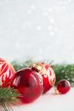 Röda prydnader och xmas-trädet blänker på feriebakgrund Glad julkort royaltyfria foton