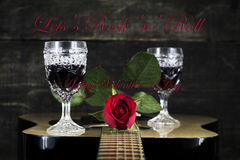 Röda ros- och vinexponeringsglas som vilar på den akustiska gitarren med tecken L Royaltyfria Bilder