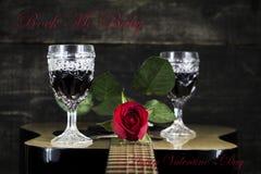 Röda ros- och vinexponeringsglas som vilar på den akustiska gitarren med tecken R Arkivfoton