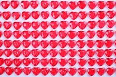 Röda rosa hjärtagodisar som i rad läggas på vit bakgrund Gåva för kort för vändaghälsning Arkivbild