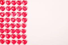 Röda rosa hjärtagodisar som i rad läggas på vit bakgrund Gåva för kort för vändaghälsning Royaltyfri Bild