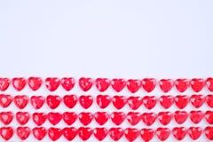 Röda rosa hjärtagodisar som i rad läggas på vit bakgrund Gåva för kort för vändaghälsning Royaltyfri Foto