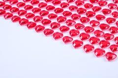 Röda rosa hjärtagodisar som i rad läggas på vit bakgrund Gåva för kort för vändaghälsning Royaltyfria Foton