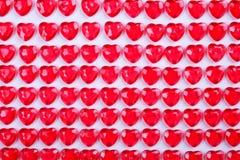 Röda rosa hjärtagodisar som i rad läggas på vit bakgrund Gåva för kort för vändaghälsning Royaltyfri Fotografi