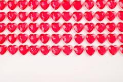 Röda rosa hjärtagodisar som i rad läggas på vit bakgrund Gåva för kort för vändaghälsning Arkivfoto