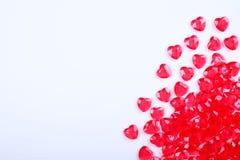 Röda rosa hjärtagodisar spridde omkring på vit bakgrund Gåva för kort för vändaghälsning Royaltyfri Bild