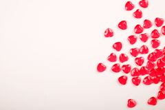 Röda rosa hjärtagodisar spridde omkring på vit bakgrund Gåva för kort för vändaghälsning Royaltyfri Foto