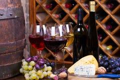 Röda, rosa och vita exponeringsglas och flaskor av vin Arkivfoto