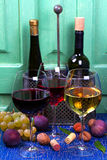 Röda, rosa och vita exponeringsglas och flaskor av vin Druva, fikonträd, muttrar och sidor på den gamla blåtttabellen Arkivbilder