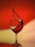 Röda Rose Wine Tempting Abstract Splashing på lutningbakgrund av gula och röda färgerna de vit, på det reflekterande Royaltyfri Bild
