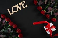 Röda rosor blommar med träordet FÖRÄLSKELSE på svart bakgrund med Royaltyfria Foton