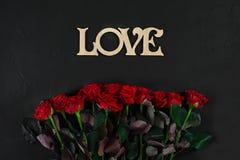 Röda rosor blommar med träordet FÖRÄLSKELSE på svart bakgrund med Arkivbilder
