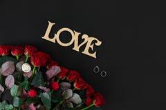 Röda rosor blommar med träordet FÖRÄLSKELSE på svart bakgrund med Royaltyfri Fotografi