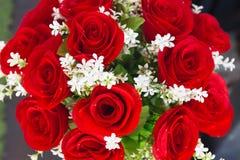 Röda rosor från konstgjorda blommor och den vita blomman Arkivbild
