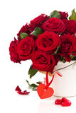 Röda rosor i hink arkivfoto