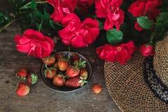 Röda rosor, jordgubbar och en hatt på en gammal tabell arkivbild