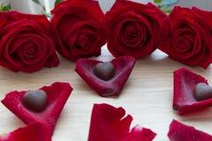 Röda rosor med choklad i kronblad Royaltyfria Bilder