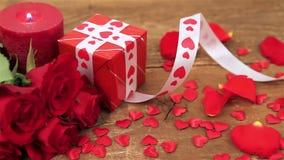 Röda rosor och gåvaask på träbakgrund arkivfilmer