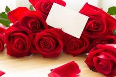 Röda rosor och kronblad på den wood tabellen med det tomma pappers- kortet Royaltyfria Bilder