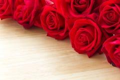 Röda rosor på den wood tabellen Fotografering för Bildbyråer