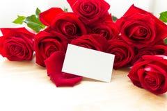 Röda rosor på den wood tabellen med det tomma pappers- kortet Arkivfoto