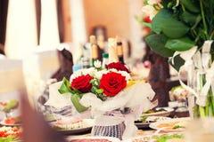 Röda rosor på en ferietabell Royaltyfri Foto