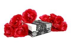 Röda rosor på en gåvaask som dekoreras med, snör åt bandet Arkivbilder