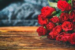 Röda rosor på en gammal trätabell Arkivfoton