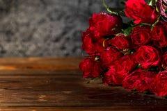 Röda rosor på en gammal trätabell Arkivbild