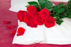 Röda rosor på en kudde och röda ark Arkivbild