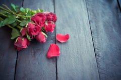 Röda rosor på wood bakgrund, Retro tappning, Arkivbilder