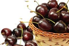 Röda söta körsbär i en korg Arkivbild