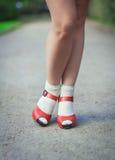 Röda sandaler med vita sockor på flicka lägger benen på ryggen i femtiotalstil Royaltyfri Bild