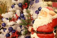 Röda Santa Claus nära julgranen arkivfoto