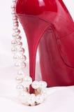 Röda sexiga skor med pärlapärlor arkivbilder