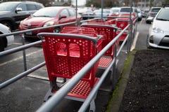 Röda shoppa vagnar på parkeringsplatsen arkivbild