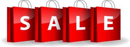 Röda shoppingpåsar med ordförsäljningen Arkivfoto