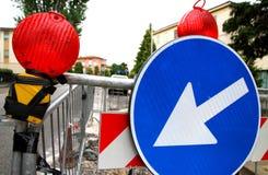 Röda signallampor och ett vägmärke för att avgränsa roadworksna i Royaltyfria Bilder