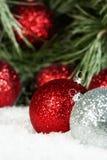 Röda silverprydnader sörjer snö Arkivfoton