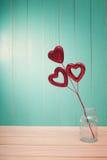 Röda skinande hjärtaprydnader på tappningträ Royaltyfri Bild