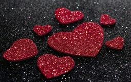 Röda skinande hjärtor på en svart bakgrund Royaltyfri Foto