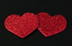 Röda skinande hjärtor på svart bakgrund Arkivbild