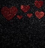 Röda skinande urblekta hjärtor på en svart bakgrund Arkivfoto