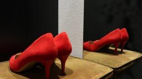 Röda skor för hög häl för mockaskinn på en svart bakgrund arkivbilder