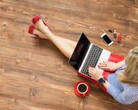 Röda skor för kvinna med bärbar datordatoren Arkivfoton