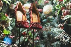 Röda skor i julgran, snö och garneringar Arkivbild
