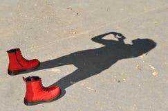 Röda skor och barnskugga arkivbild
