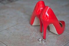 Röda skor och vigselringar Arkivfoto
