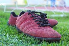 Röda skor på grönt gräs med målfotboll Arkivfoto